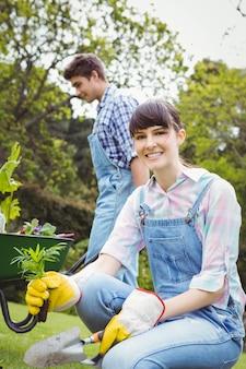 Jonge vrouw die een jong boompje in tuin planten