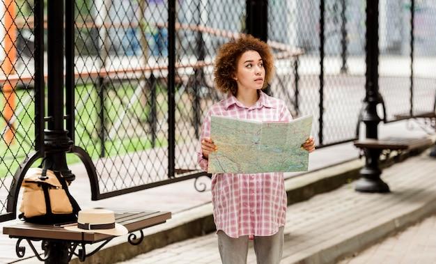 Jonge vrouw die een kaart voor een nieuwe bestemming controleert