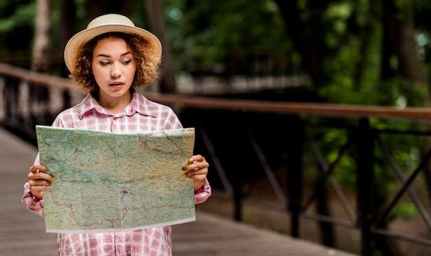 Jonge vrouw die een kaart voor een nieuwe bestemming met exemplaarruimte controleert