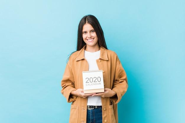 Jonge vrouw die een kalender van de jaren 2020 gelukkig, glimlachend en vrolijk houdt