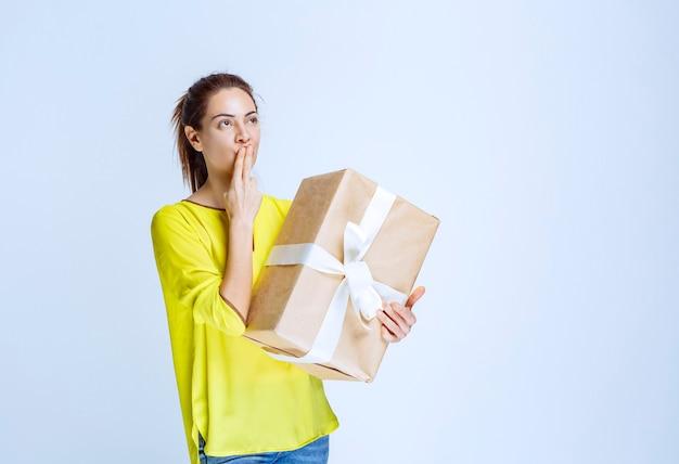 Jonge vrouw die een kartonnen geschenkdoos vasthoudt en denkt aan de onbekende afzender