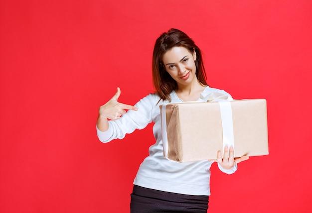 Jonge vrouw die een kartonnen geschenkdoos vasthoudt en er verrast en blij uitziet