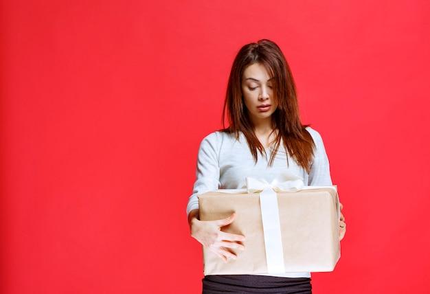 Jonge vrouw die een kartonnen geschenkdoos vasthoudt en er verward en attent uitziet