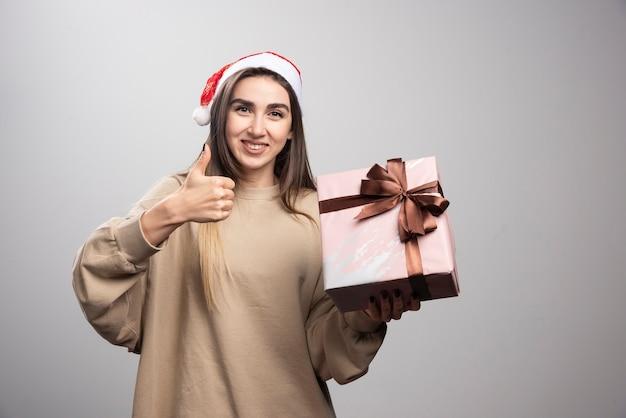 Jonge vrouw die een kerstcadeau houdt en een duim toont.