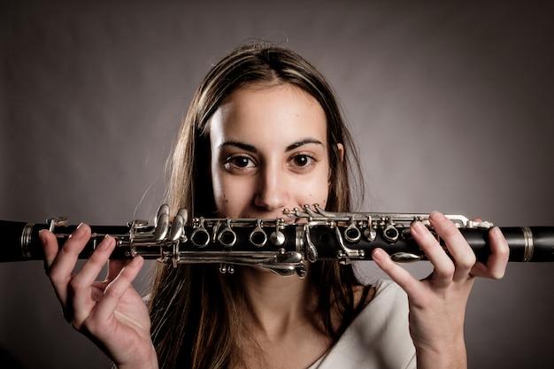 Jonge vrouw die een klarinet op grijs houdt