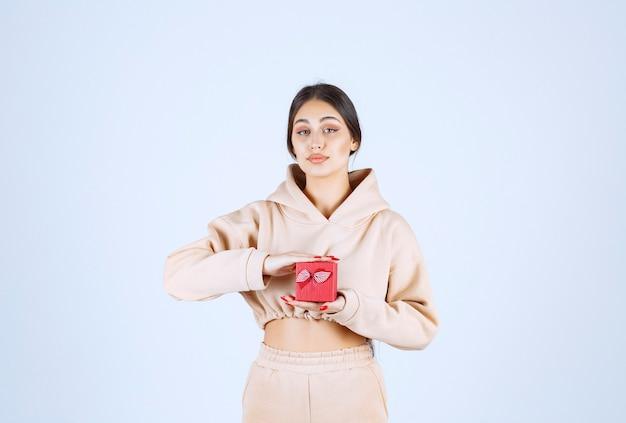 Jonge vrouw die een kleine rode giftdoos met beide handen houdt