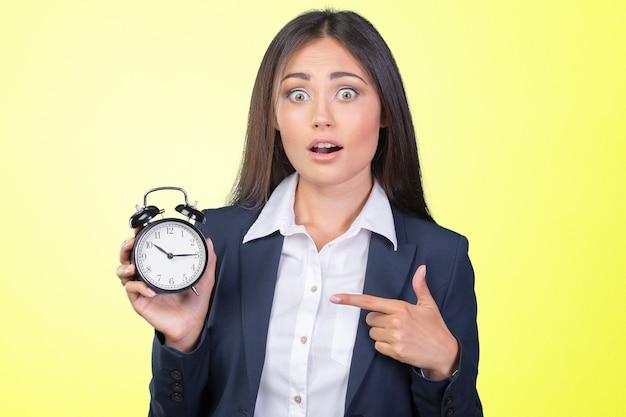 Jonge vrouw die een klok houdt. time management concept.