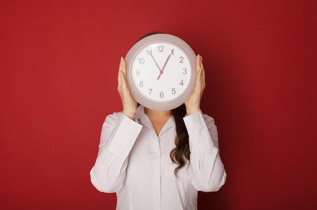 Jonge vrouw die een klok op een rood houdt.