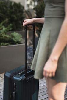 Jonge vrouw die een koffer houdt