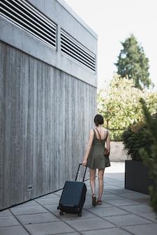Jonge vrouw die een koffer leidt