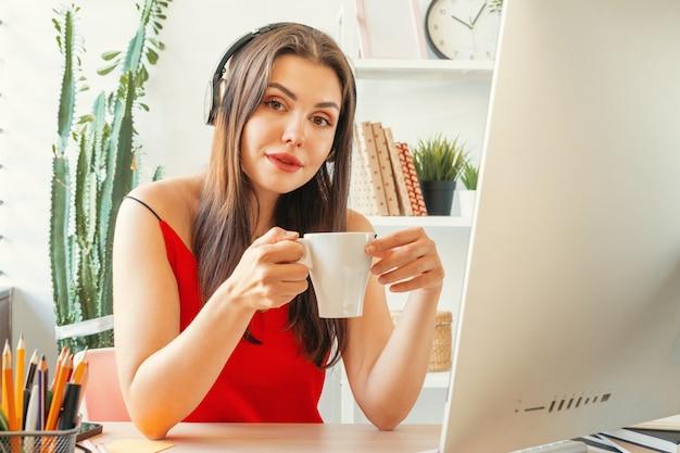 Jonge vrouw die een koffiepauze heeft terwijl het zitten in haar kantoor