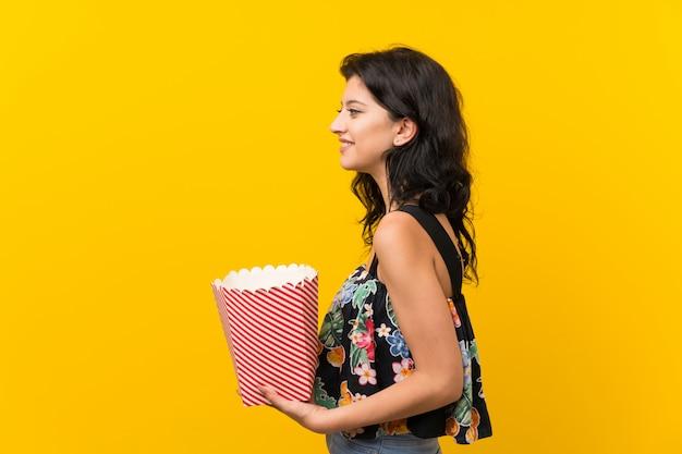 Jonge vrouw die een kom popcorns houdt