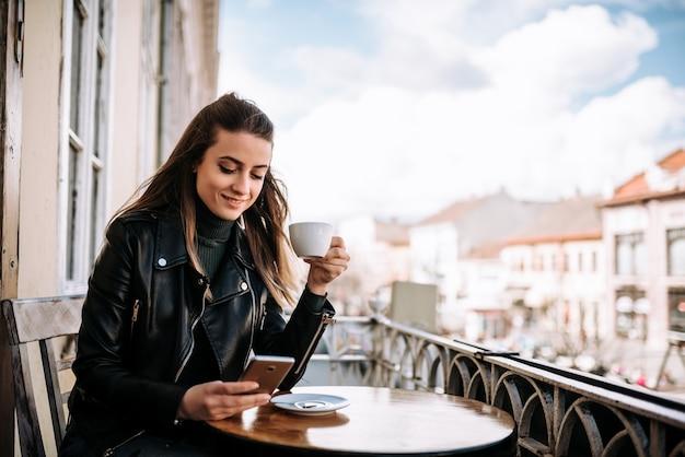 Jonge vrouw die een kop van koffie in openlucht drinkt.