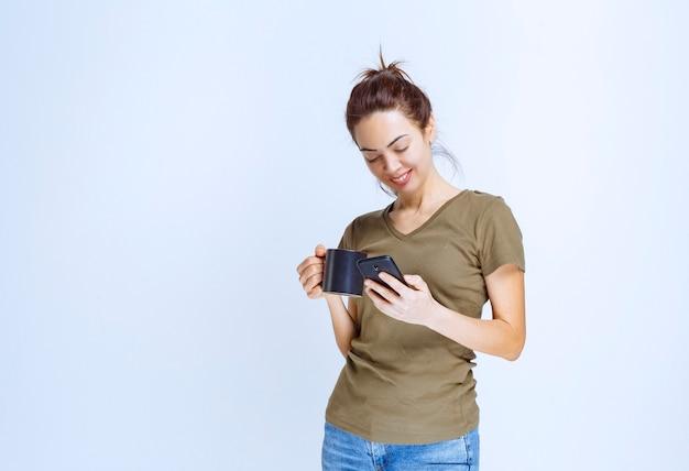 Jonge vrouw die een kopje koffie vasthoudt en tegen de telefoon praat