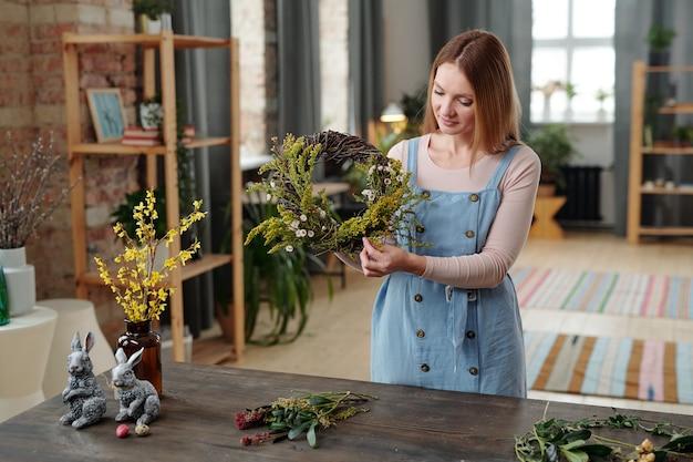 Jonge vrouw die een krans maakt van bloemen en planten voor de vakantie