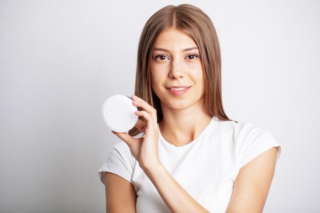 Jonge vrouw die een kruik huidzorgroom houdt