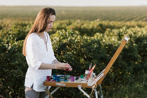 Jonge vrouw die een kunstwerk schildert