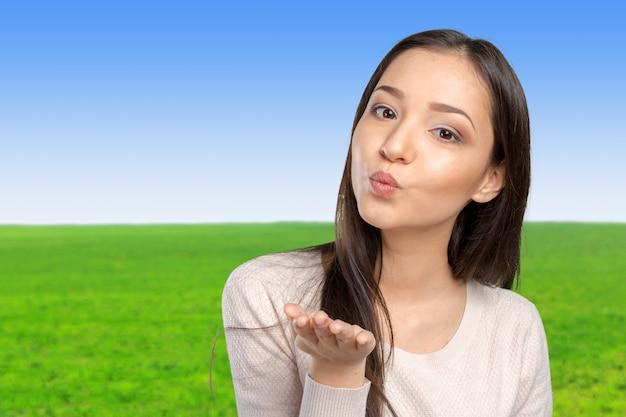 Jonge vrouw die een kus blaast