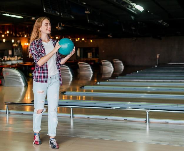 Jonge vrouw die een lang schot van de kegelenbal houdt