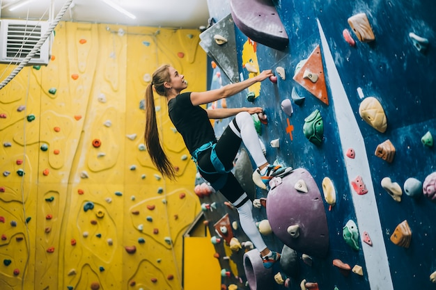 Jonge vrouw die een lange, binnen, kunstmatige klimmuur beklimt