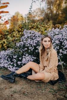 Jonge vrouw die een lange chiffonjurk en leerlaarzen draagt die door een struik met purpere bloemen zitten