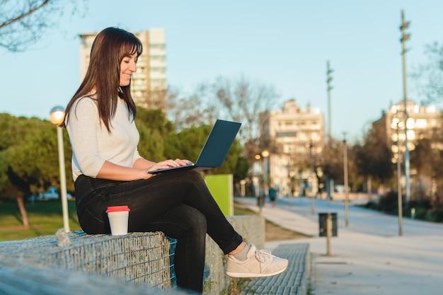 Jonge vrouw die een laptop computer op straat met behulp van. freelance werkconcept.