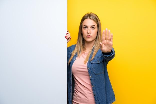 Jonge vrouw die een leeg aanplakbiljet houdt dat eindegebaar met haar hand maakt