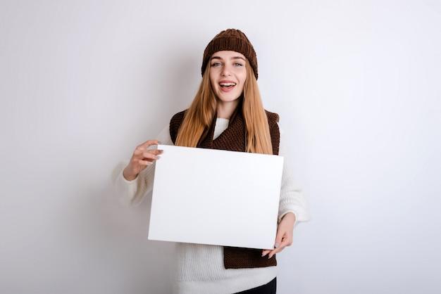 Jonge vrouw die een leeg teken vooraan houdt oh haar gezicht