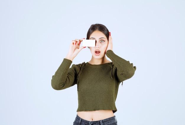 Jonge vrouw die een leeg visitekaartje toont en haar oor bedekt.