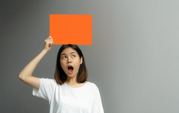 Jonge vrouw die een lege affiche voor tekst op een witte achtergrond houdt.
