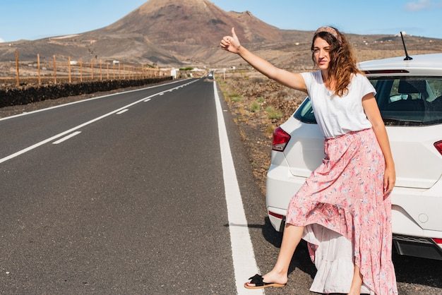 Jonge vrouw die een lekke band heeft gehad in een autowiel die met opgeheven duim lift