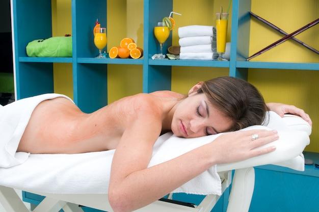Jonge vrouw die een lichaamsbehandeling krijgt op een massageplaats