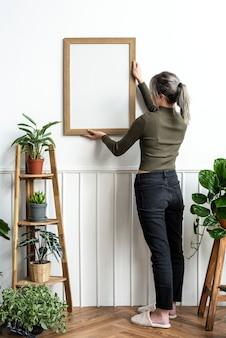 Jonge vrouw die een lijst aan de muur hangt