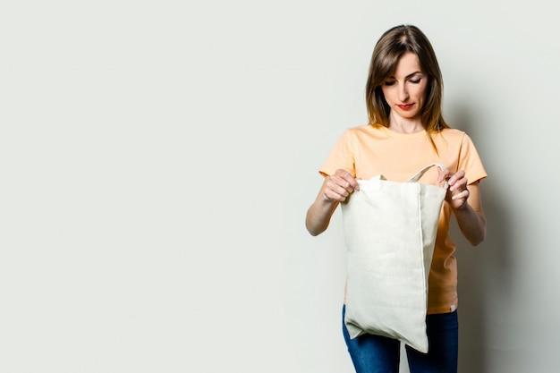 Jonge vrouw die een linnenzak onderzoeken met het winkelen op een lichte achtergrond