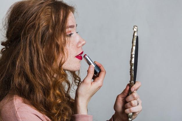 Jonge vrouw die een lippenstift gebruikt