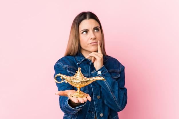 Jonge vrouw die een magische lamp houdt