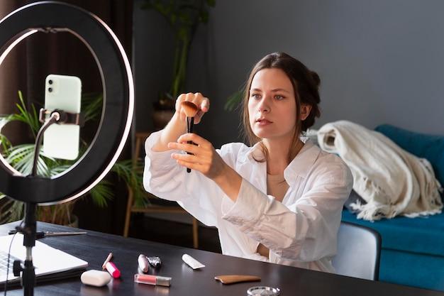 Jonge vrouw die een make-upvlog maakt met haar smartphone