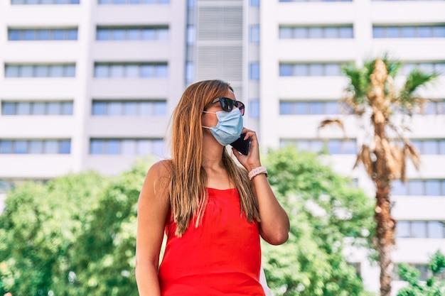 Jonge vrouw die een masker draagt dat op een mobiele telefoon in de stad spreekt