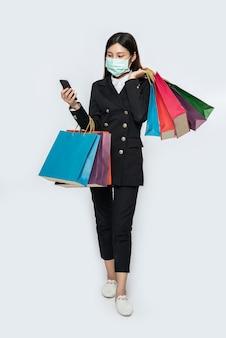 Jonge vrouw die een masker draagt en op haar smartphone winkelt