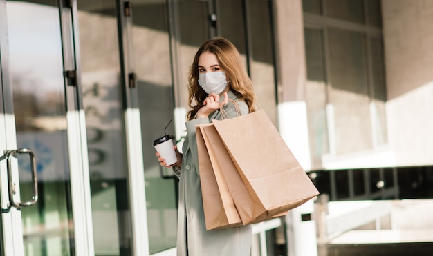 Jonge vrouw die een masker draagt om het virus te voorkomen met boodschappentassen in de smalle straat in europa.