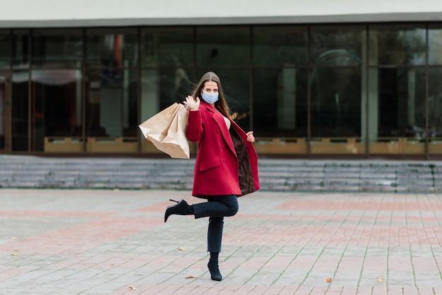 Jonge vrouw die een masker draagt om het virus te voorkomen met boodschappentassen op een smal straatje in europa.