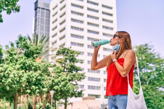 Jonge vrouw die een masker drinkwater draagt in de stad