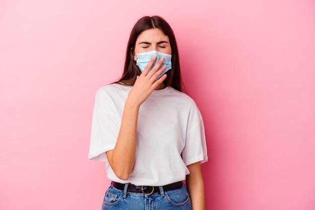 Jonge vrouw die een masker voor virus draagt dat op roze muur wordt geïsoleerd die geeuwt die een moe gebaar toont dat mond met hand bedekt