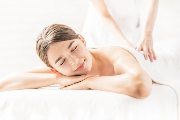 Jonge vrouw die een massage ontvangt bij een schoonheidssalon