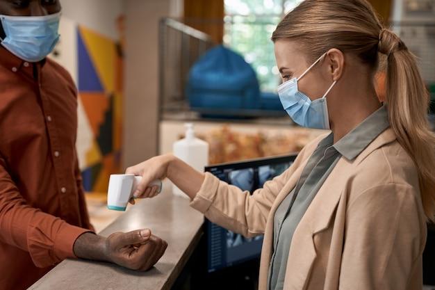 Jonge vrouw die een medisch gezichtsmasker draagt dat bij de receptie op kantoor staat en het lichaam meet