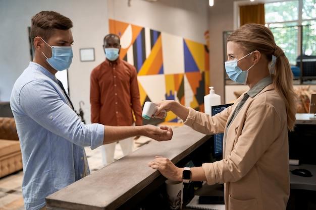 Jonge vrouw die een medisch gezichtsmasker draagt dat bij de receptie op kantoor staat en infrarood gebruikt