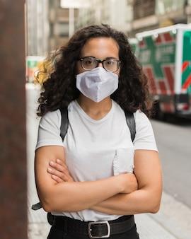 Jonge vrouw die een medisch masker buiten draagt
