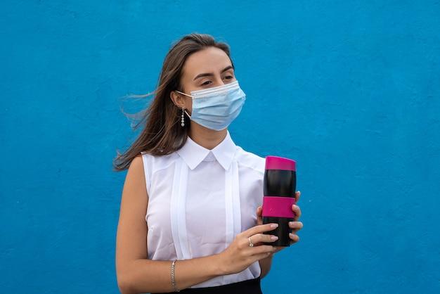 Jonge vrouw die een medisch masker draagt als gevolg van een coronavirusinfectie en een mok koffie vasthoudt