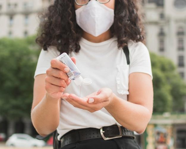 Jonge vrouw die een medisch masker draagt dat handdesinfecterend middel gebruikt