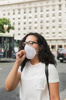 Jonge vrouw die een medisch masker draagt en in openlucht hoest